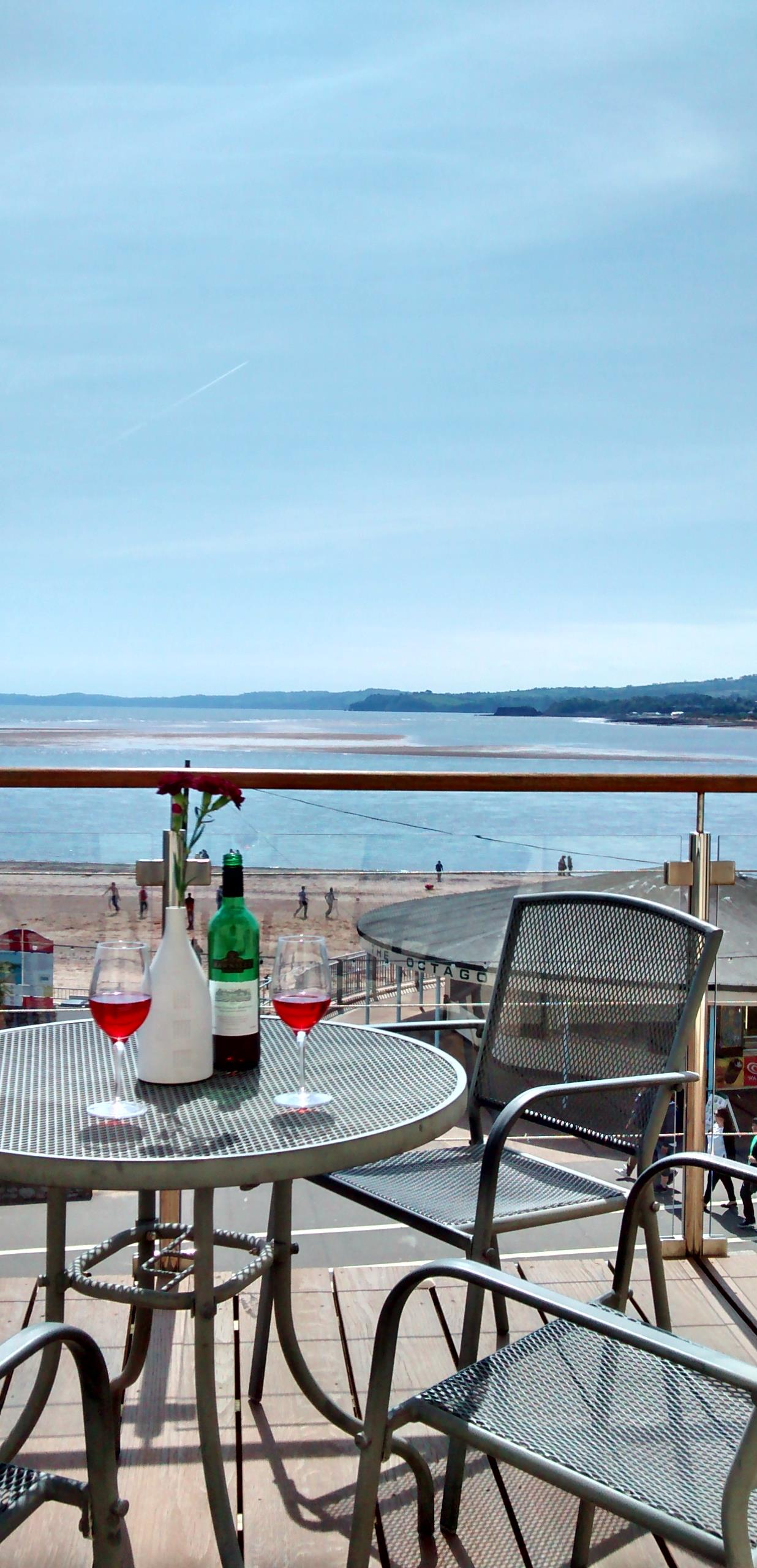 View across balcony table with wine bottle out to sea